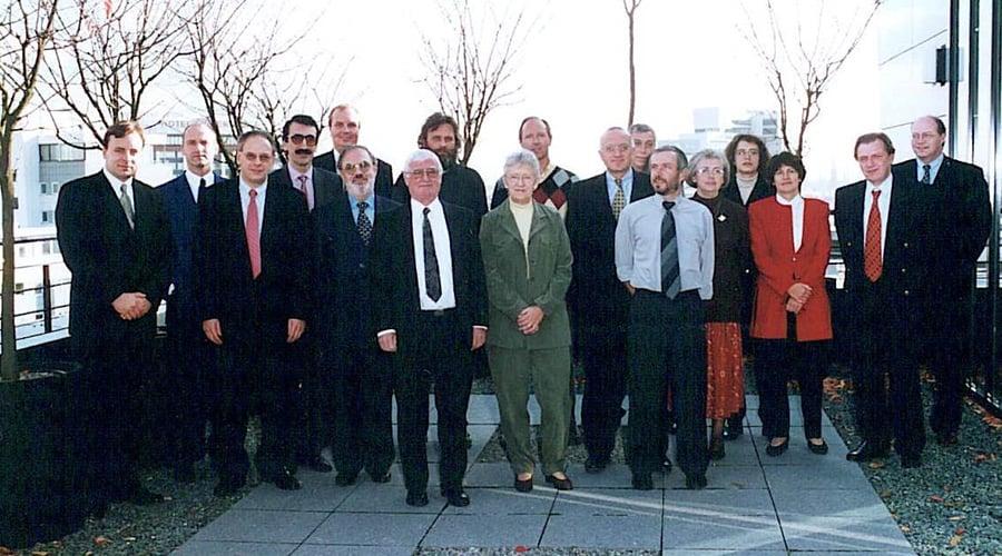 Bilde (fotograf: DIN- det tyske standardiseringsinstituttet): Fra det siste møtet i CEN/TC328 i Berlin i november 1999. Foran i midten; Anne-Lise Schjønning, INSTA800s mor. Bak henne til høyre; Johannes Bungart, leder for arbeidet i CEN. I midten bakerst; Tormod Jarsve (med mye hår og skjegg) flankert av Jan Stiiskjær (til venstre) og undertegnede (til høyre). Ytterst til venstre; sekretariatsleder Holger Mühlbauer, ytterst til høyre; initiativtaker Freek Veneman.
